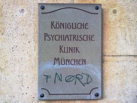 Schild an einem Eingang: 'Königliche Psychiatrische Klinik München'. Graffito darunter: 'FNORD'.