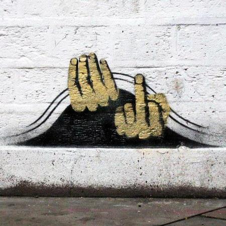 Graffito an der unteren Seite einer Hauswand. Eine Hand schiebt einen Vorhang hoch, die andere Hand zeigt dem Betrachter einen Stinkefinger.