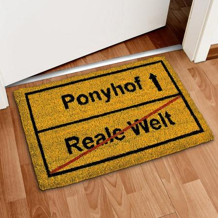 Fußmatte mit einem Aufdruck im Stil eines Ortsausgangsschildes. Der Ort 'Reale Welt' wird verlassen, der nächste Ort heißt 'Ponyhof'.
