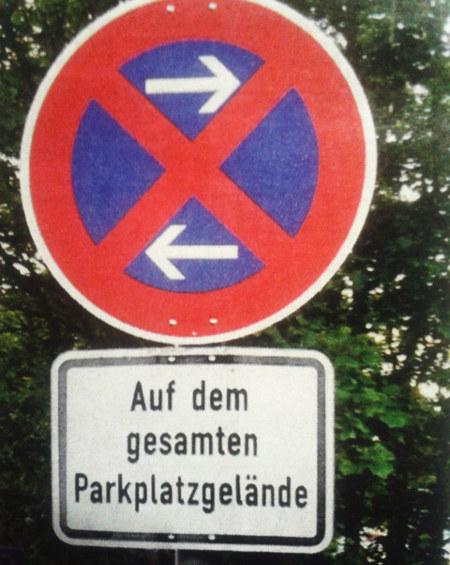 Verkehrszeichen 'Absolutes Halteverbot' mit Zusatzschild 'Auf dem gesamten Parkplatzgelände'.