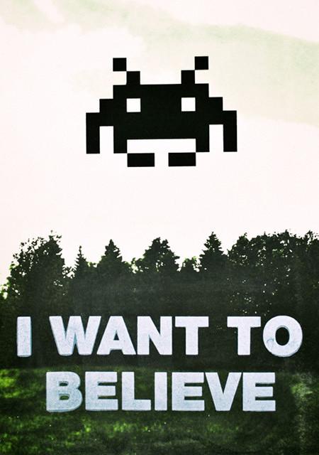 Ein pixeliges Wesen aus »Space Invaders« über einem Waldstück, darunter der Text »I want to believe«.