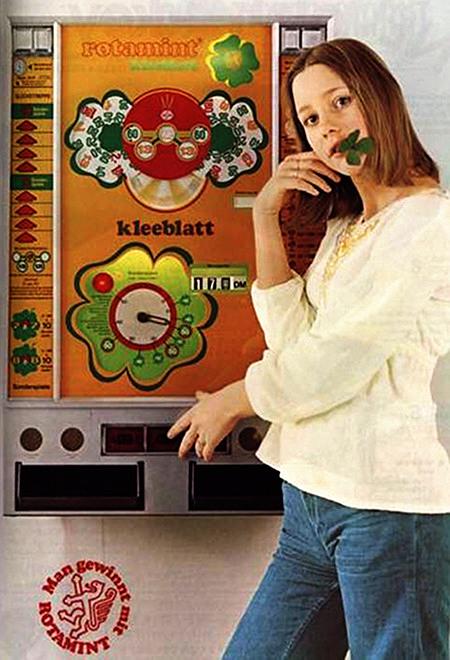 Werbung für das NSM-Geldspielgerät Rotamint Kleeblatt aus dem Jahr 1975 -- Eine Zierfrau schaut vom Automaten weg und drückt in seltsamer Haltung auf eine Taste, im Mund trägt sie ein Kleeblatt. Dazu der damalige NSM-Claim: Man gewinnt mit Rotamint