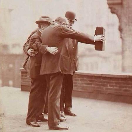 Foto aus dem Jahr 1920. Drei Männer halten eine unhandliche Kamera der damaligen Zeit auf Armeslänge von sich weg, um ein Selfie zu machen.