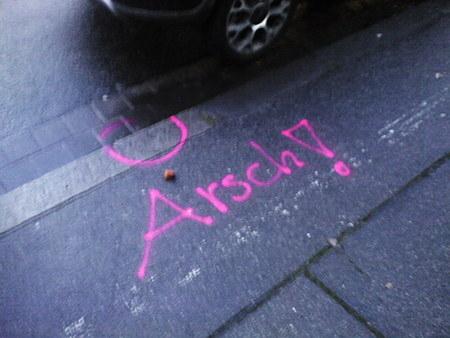 Graffiti auf einer Straße: Arsch!