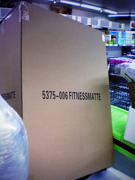 Schmuckloser Pappkarton in einem Aldi-Nord-Markt, mit Aufdruck 5376-006 Fitnessmatte