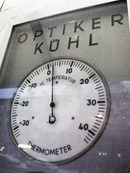 Außenwerbung eines 'Optiker Kühl' mit einem Thermometer, das zwei Grad Celsius anzeigt.