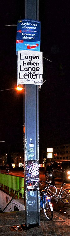 Weit oben an einem Stahlträger angebrachtes Wahlplakat der AfD mit dem Slogan 'Asylchaos stoppen! Grenzen sichern!'. Direkt darunter ist eine Pappe mit der handgeschriebenen Aufschrift 'Lügen haben lange Leitern. Antifa GmbH.' angebracht.
