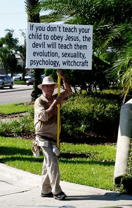 Mann, der ein Schild hochhält: If you don't teach your child to obey Jesus, the devil will teach them evolution, sexuality, psychology, witchcraft