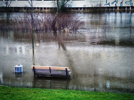 Hochwasser an der Ihme. Eine Bank steht im Wasser, daneben ein Mülleimer. Im Hintergrund Sträucher dort, wo das Ufer war, dahinter der brutalistische Betonbau des Ihmezentrums. Das Ihmezentrum spiegelt sich im gekräuselten Wasser.