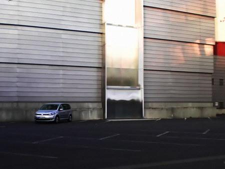 Gnadenlos tristes Bild eines einzelnen Autos auf einem Werksparkplatz in schönem Abendlicht