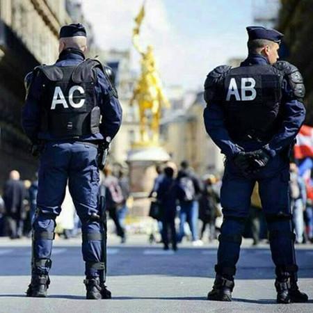 Die Rücken zweier nebenaneinderstehender Polizisten in Uniform. Der linke hat auf dem Rücken die Buchstaben 'AC' stehen, der rechte 'AB'.