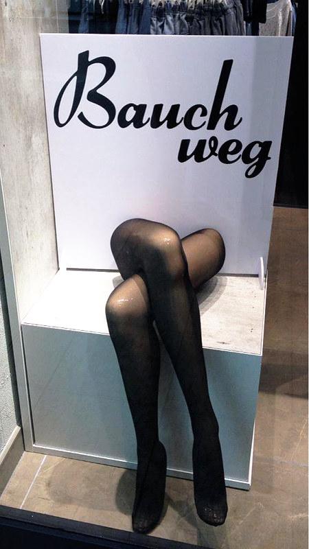 Obskure Schaufensterdekoration. Unter dem Worten 'Bauch weg!' befinden sich zwei übereinandergelegte, mit Strumpfhosen überzogene Beine einer Schaufensterpuppe, als würde dort eine Frau ohne Oberkörper sitzen.