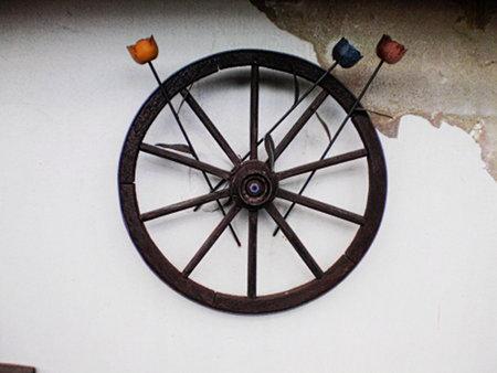 Dekoration in einem Kleingarten. An einer Wand der Gartenlaube, deren Putz großflächige Schäden hat, hängt ein hölzernes Wagenrad. In die Speichen des Rades sind drei extrem hässliche, blumenförmige Dekorationsobjekte aus Metall eingeflochten, die wohl mal intensiv gelb, rot und blau gefärbt waren, aber inzwischen ausgeblichen sind und sichtbar korrodieren.