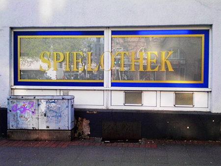 Fenster einer Spielhalle, undurchsichtig, mit aufgeklebtem Schriftzug 'Spielothek', schäbig anmutend
