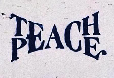 Graffito. Die Wörter 'Teach Peace' sind in eleganter Weise so angeordnet, dass die drei gemeinsamen Buchstaben E, A, und C von beiden Wörtern geteilt werden.