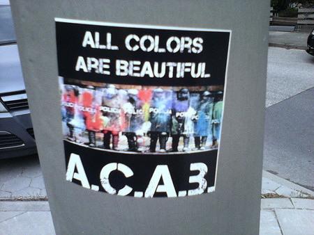 Bild von Polizisten in voller Gewaltmontur, die mit Farbbeuteln beworfen wurden. Dazu der Text: 'All colors are beautiful'
