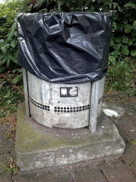 Heruntergekommener Mülleimer in einem Park. Auf dem Mülleimer ein Aufkleber mit dem Wort 'Antiking'.