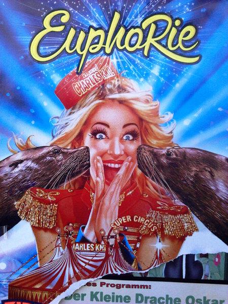 Völlig durchgeknallte, mit Worten kaum zu beschreibende Plakatwerbung für einen Zirkus. Das Gesicht einer uniformierten Frau wird von Wellen synthetischen Glücks zu einer lachenden Fratze verzerrt, während sie von zwei Seehunden scheinbar geküsst wird. Darüber das Wort 'Euphorie'.