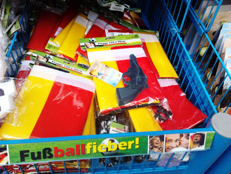 Auslage eines Ramschladens. Eine Spielzeugpistole liegt auf schwarz-rot-goldenen Flaggen. Dazu die Werbung 'Fußballfieber'.