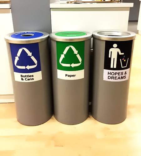 Drei Mülltonnen nebeneinander. Auf der linken steht 'Bottles and Cans', auf der mittleren steht 'Paper' und auf der rechten steht 'Hopes and Dreams'.