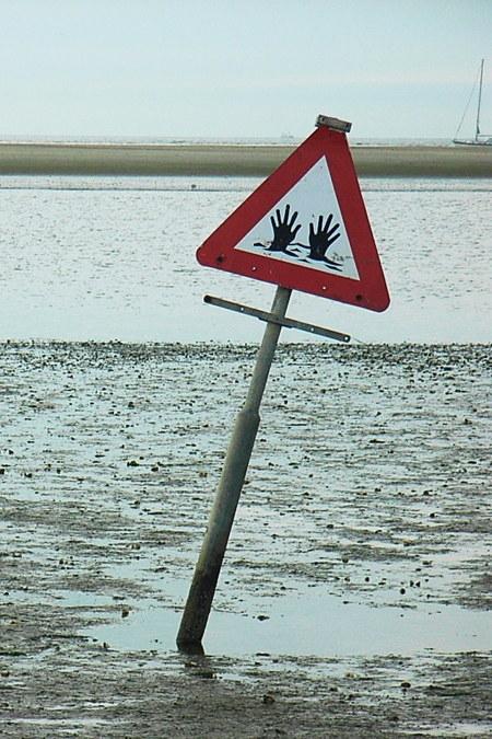 Warnschild im Treibsand. Piktogramm sind zwei Hände, die aus der Oberfläche herausschauen. Der Mast, an dem das Schild aufgestellt wurde, hat sich bereits deutlich zur Seite geneigt.