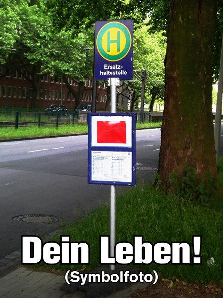 Foto eines Aufstellers mit dem Aufdruck 'Ersatzhaltestelle' für eine provisorische Bushaltestelle am Straßenrand. Dazu der Text: 'Dein Leben! (Symbolfoto)'.