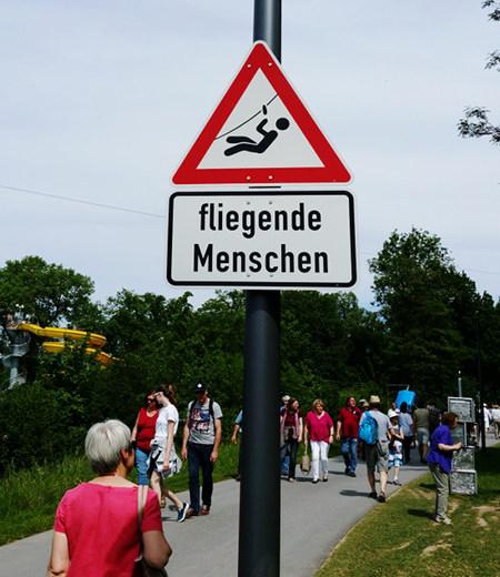Verkehrsschild mit der Warnung 'Fliegende Menschen'.