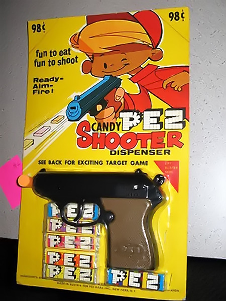 PEZ-Dispenser in Form einer Handfeuerwaffe mit dem Claim 'fun to eat, fun to shoot'