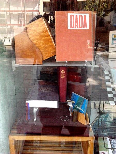 Stillleben im Schaufenster eines hannöverschen Antiquariates. Oben steht ein Buch mit dem Titel Dada, darunter liegen zwei Bibeln