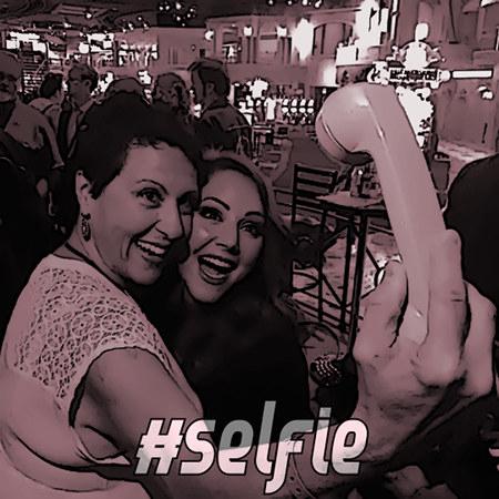 Zwei Frauen halten lächelnd die Telefonhörer eines alten, analogen Telefones, als ob sie ein Selfie machten. Darunter der Text #Selfie.