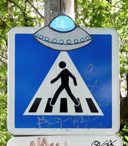 Verkehrszeichen 'Fußgängerüberweg'. Ein Graffiti-Künstler hat im oberen Bereich eine Fliegende Untertasse angebracht, so dass es im Zusammenhang mit dem weißen Dreieck so aussieht, als würde der Fußgänger in einem Lichtkegel in das UFO gezogen.