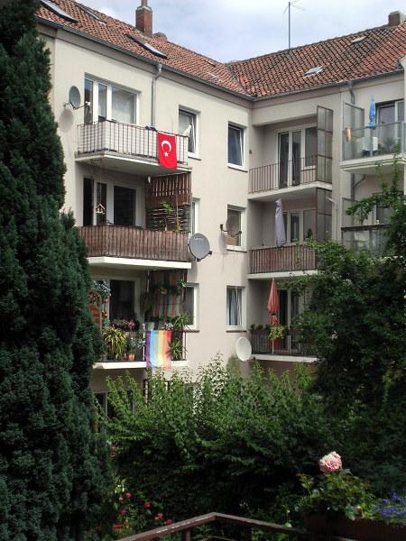 Balkone in der hannöverschen Südstadt. An einem hängt eine schwarz-rot-goldene BRD-Flagge, an einem anderen eine Regenbogenflagge, an einem dritten eine türkische Flagge