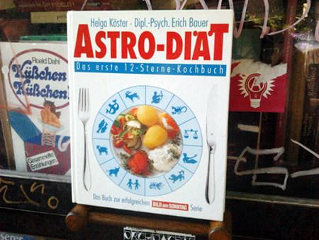 Fotografiertes Buch: Helga Köster - Dipl.-Psych. Erich Bauer -- Astro-Diät -- Das erste 12-Sterne-Kochbuch -- Darunter ein Bild eines Tellers, dessen Rand durch einen astrologischen Tierkreis überdeckt wurde, Messer und Gabel liegen daneben -- Das Buch zur erfolgreichen Bild am Sonntag Serie