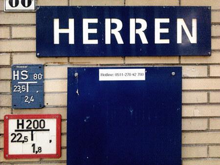 Hinweisschild am Eingang zu einer öffentlichen Toilette am hannöverschen Maschsee: Herren. Darunter ein Aufkleber mit einer Hotline-Telefonnummer