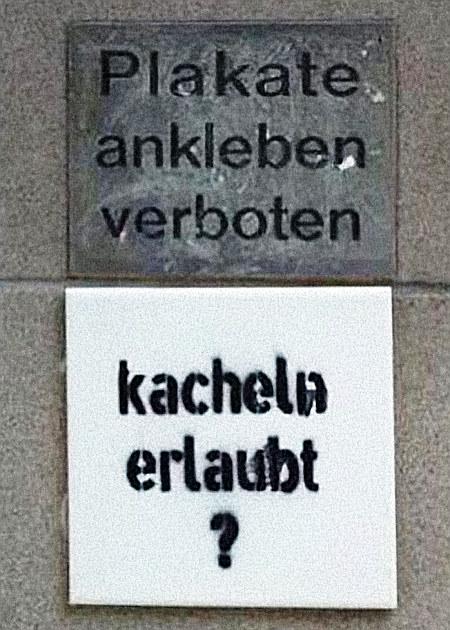 Schild an einer Hauswand: 'Plakate ankleben verboten'. Darunter eine aufgeklebte Kachel mit aufgesprühtem Text: 'Kacheln erlaubt?'.