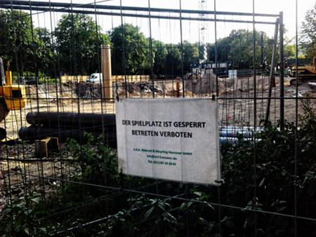 Absperrung vor einer großen Baustelle. An der Absperrung ein Schild: 'Der Spielplatz ist gesperrt -- Betreten verboten'.