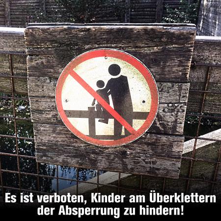 Piktografisches Verbotsschild, das verbietet, Kinder über den Zaun hochzuheben. Darunter mein Text, der genau so gut zum gleichen Piktogramm passt: Es ist verboten, Kinder am Überklettern der Absperrung zu hindern!