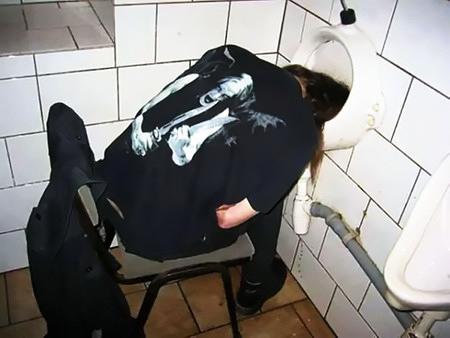 Ein offenbar alkoholisierter Jugendlicher sitzt auf einem Stuhl vor einem Pissbecken, ist eingeschlafen, der Kopf liegt im Pissbecken versenkt