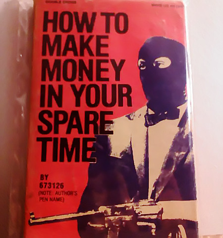 Bucheinband, der als Illustration einen fein gekleideten Mann mit Sturmmaske und Handfeuerwaffe zeigt. Titel des Buches: 'How to make money in your spare time' von 673126 (Note: author's pen name)