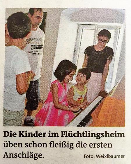 Aus einer Zeitung: Foto von Kindern am Klavier. Darunter der Text 'Die Kinder im Flüchtlingsheim üben schon fleißig die ersten Anschläge.'