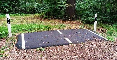 Foto eines absurden, ca. 30cm langen Straßenstückes mitten im Wald