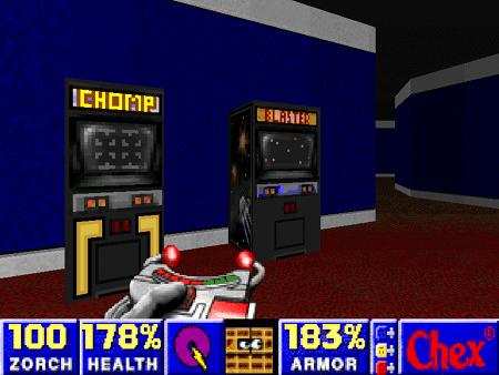 Screenshot aus Chex Quest 3: Zwei Arcade-Cabinets mit den Titeln 'Chomp' und 'Blaster' stehen in einem Gang.