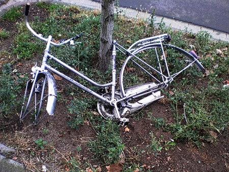 Ausgeweidetes Fahrrad, in der Stadt auf eine winzige Grünfläche hingeworfen