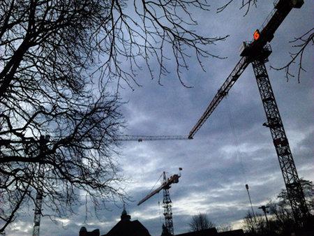 Kräne auf einer Baustelle und novemberkahle Bäume recken sich dem grauen, trüben, lichtgeizigen Himmel entgegen