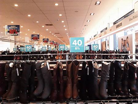 Inneres eines Schuhgeschäftes. Im Vordergrund Stiefel, Größe 40, ganz viele Tafeln mit der Größenangabe 40, an der Decke Hinweisschilder 'Schöne Bescherung, 50% reduziert'.