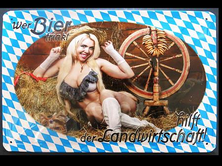 Absurde sexistische Darstellung einer leicht bekleideten Frau mit großen Dingern im Stroh, eingerahmt von weiß-blauen Rauten. Dazu der Text: 'Wer Bier trinkt, hilft der Landwirtschaft'.