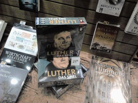 Foto eines Schaufensters einer Buchhandlung. Darin gut sichtbar ein Buch 'Wirtschaft verstehen', ein Karton 'Luther -- Das Spiel' und ein Buch 'Säulen des Himmels, Houses of God'.