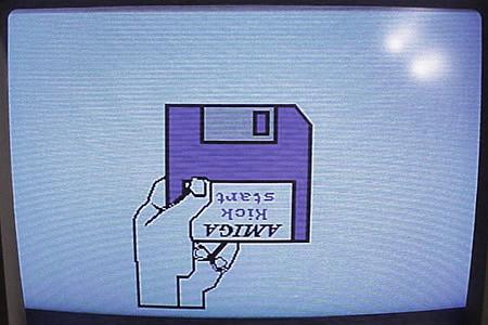 Einschaltbildschirm des Amiga 1000, der mit einem bildschirmfüllenden Piktogramm das Einlegen einer Kickstart-Diskette anfordert