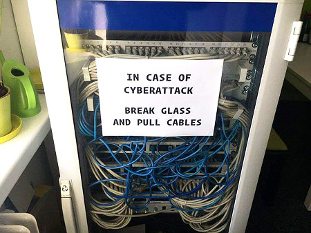 Aufgeklebter Zettel auf einen Serverschrank voller Router: 'In case of cyberattack: Break glass and pull cables'.