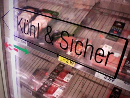 Schiebetür an einem Gefrierschrank in einem Supermarkt mit dem Aufkleber 'Kühl & Sicher'.